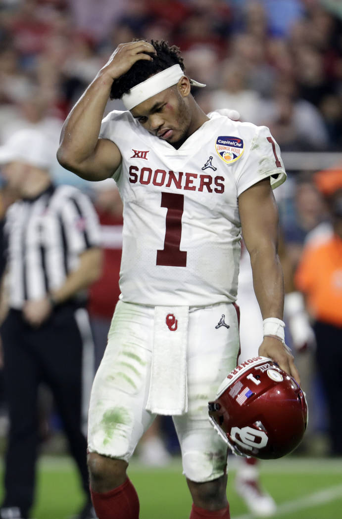 Oklahoma quarterback Kyler Murray (1) walks off the field after his helmet came off on a play, ...