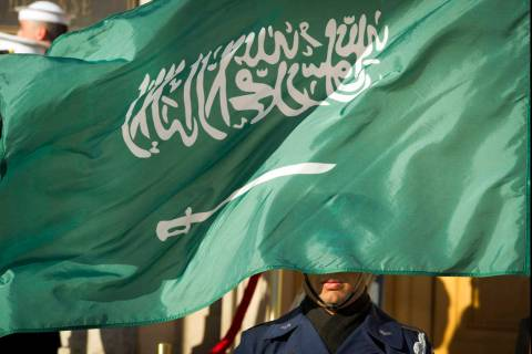 FILE - In this March 22, 2018 file photo, an Honor Guard member is covered by the flag of Saudi ...