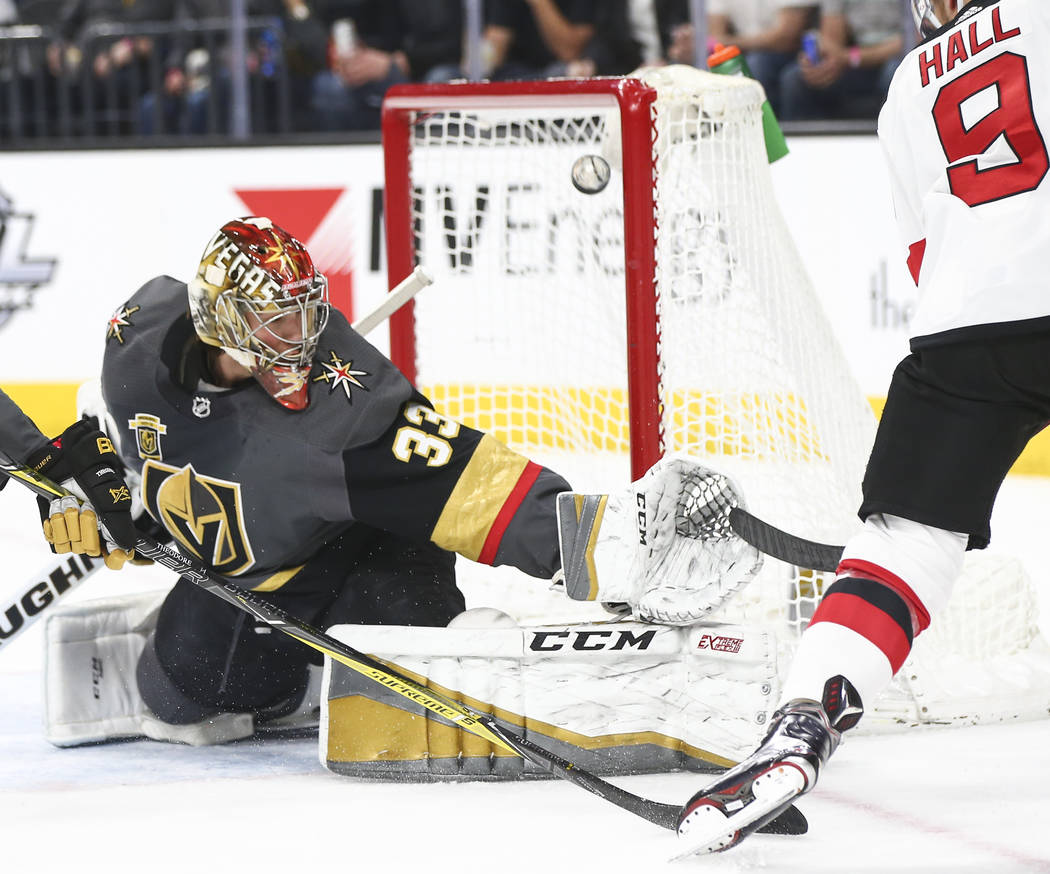 Golden Knights goaltender Maxime Lagace (33) blocks a shot from New Jersey Devils left wing Tay ...