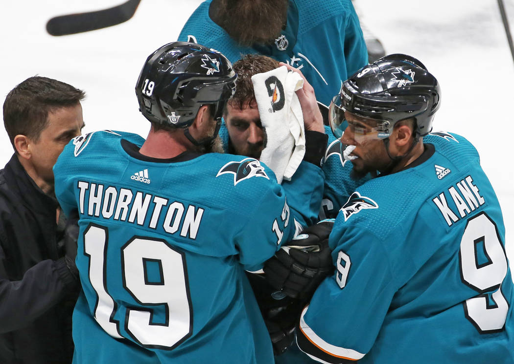 Sharks center Joe Pavelski, middle, is helped off the ice by Sharks left wing Evander Kane and ...