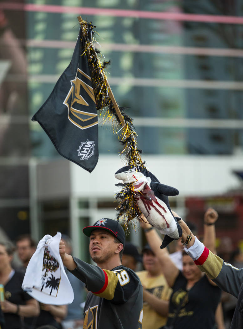 A Golden Knights fan flies a flag with bloody shark attached while celebrating a goal with othe ...