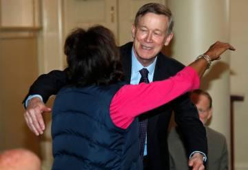 Democratic presidential hopeful John Hickenlooper, back, hugs Colorado state Sen. Rhonda Fields ...