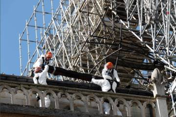 Workers install protections on Notre Dame cathedral Wednesday, April 24, 2019 in Paris. Profess ...