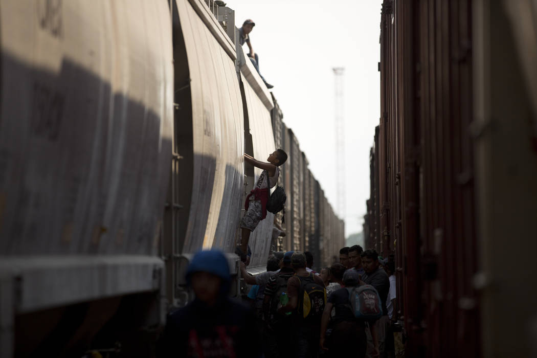 Central American migrants climb on a parked freight train during their journey toward the U.S.- ...