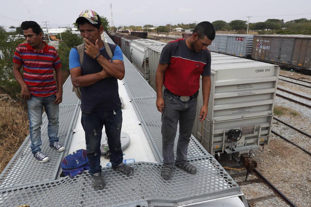 Honduran migrants Jose Francisco Mendez, left, Denis Funes, center, and Jose Mendoza stand on t ...