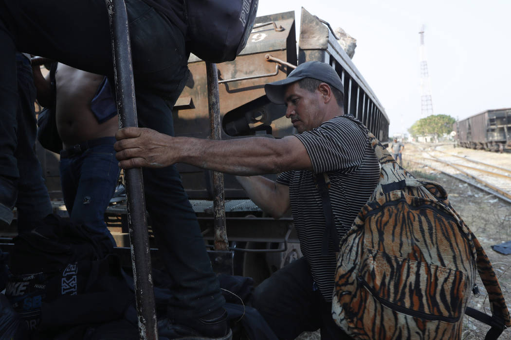 A Central American migrant climbs on a freight train on is way to the U.S.-Mexico border, in Ix ...