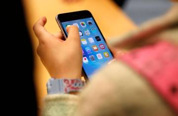 A child holds an Apple iPhone 6S on Sept. 25, 2015, at an Apple store on Chicago's Magnificent ...