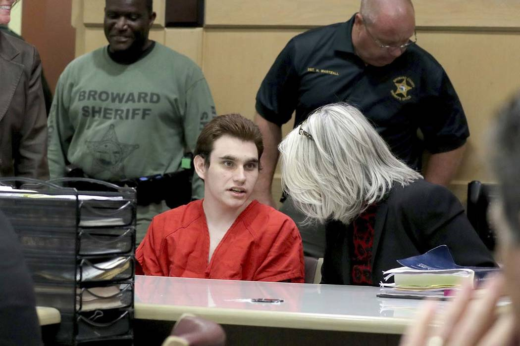 Parkland school shooting suspect Nikolas Cruz speaks with his attorney in court for a defense m ...