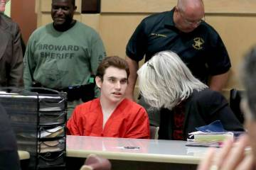 Parkland school shooting suspect Nikolas Cruz speaks with his attorney in court for a defense m ...
