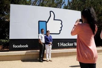 Visitors take photos in front of the Facebook logo Aug. 31, 2016, outside of the company's head ...