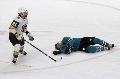 San Jose Sharks center Joe Pavelski, right, lies on the ice next to Vegas Golden Knights center ...