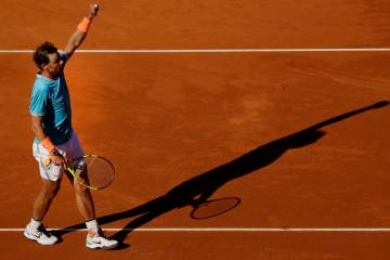 Spain's Rafael Nadal raises his arm after winning his men's singles match against Argentina's L ...