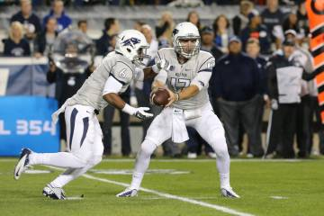 UNR quarterback Cody Fajardo (17) hands the ball off to running back Don Jackson (6) against Br ...