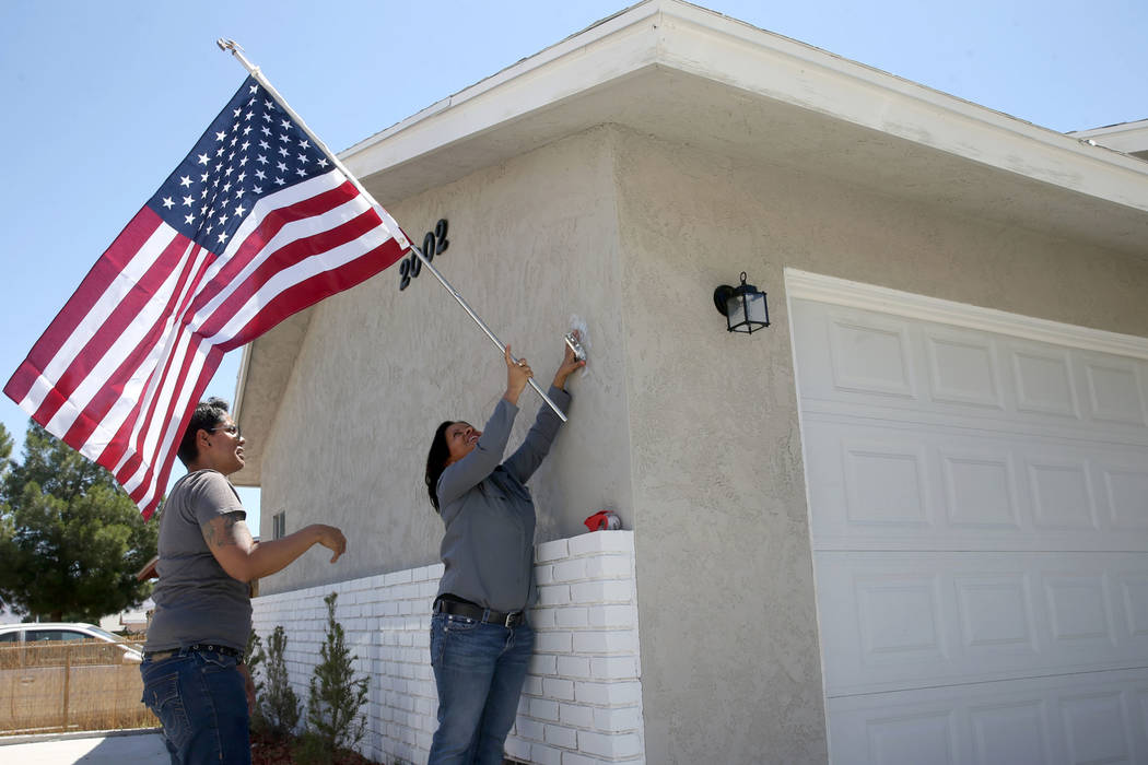 Ana Martinez, a veteran who was homeless two years ago, hangs the American flag for the first t ...