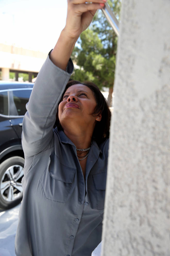 Ana Martinez, a veteran who was homeless two years ago, cries as she hangs the American flag fo ...