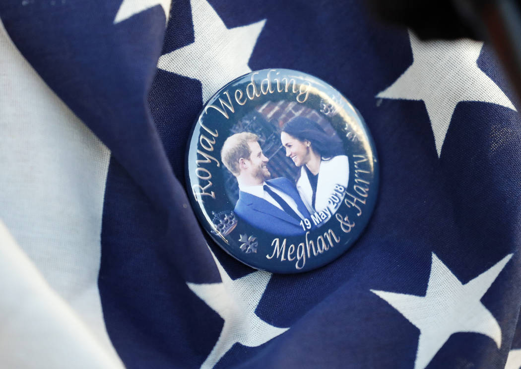 FILE- In this Thursday, May 17, 2018 file photo, a badge showing Prince Harry and Meghan Markle ...