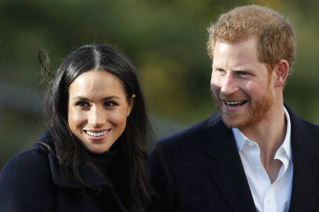 FILE - In this Dec. 1, 2017 file photo, Britain's Prince Harry and his fiancee Meghan Markle ar ...