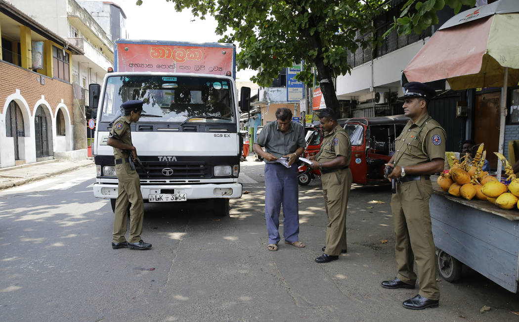 Sri Lankan police officers perform security checks on a truck at a roadside in Colombo, Sri Lan ...