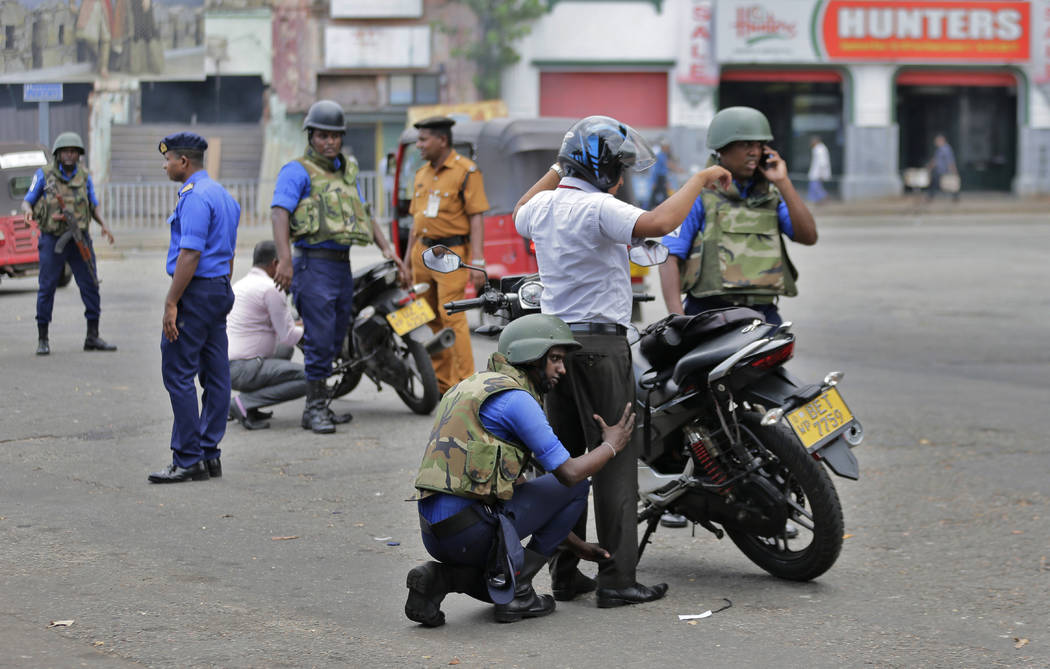 Sri Lankan navy soldiers perform security checks on motorists at a road in Colombo, Sri Lanka, ...