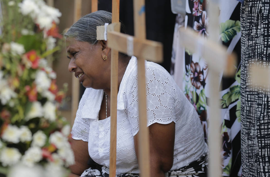 An elderly Sri Lankan woman cries sitting next to the grave of her family member who died in Ea ...