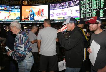 Fans lined up to place their bets during the first day of the NCAA basketball tournament at the ...