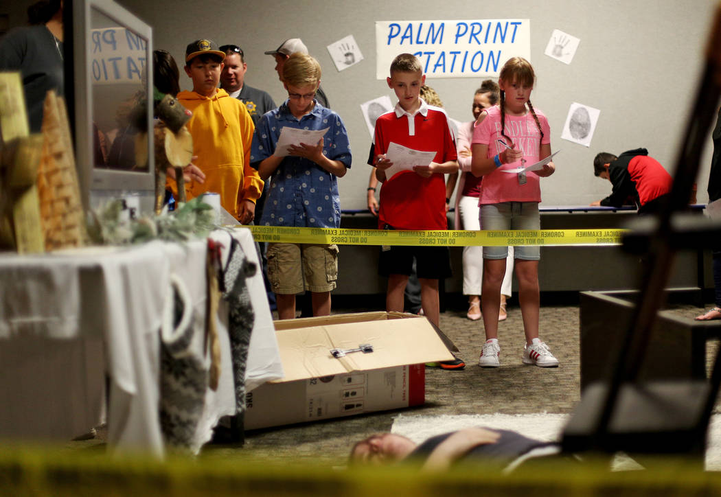 Children examine a fake crime scene for the coroner office's Take Our Daughters and Sons to Wor ...
