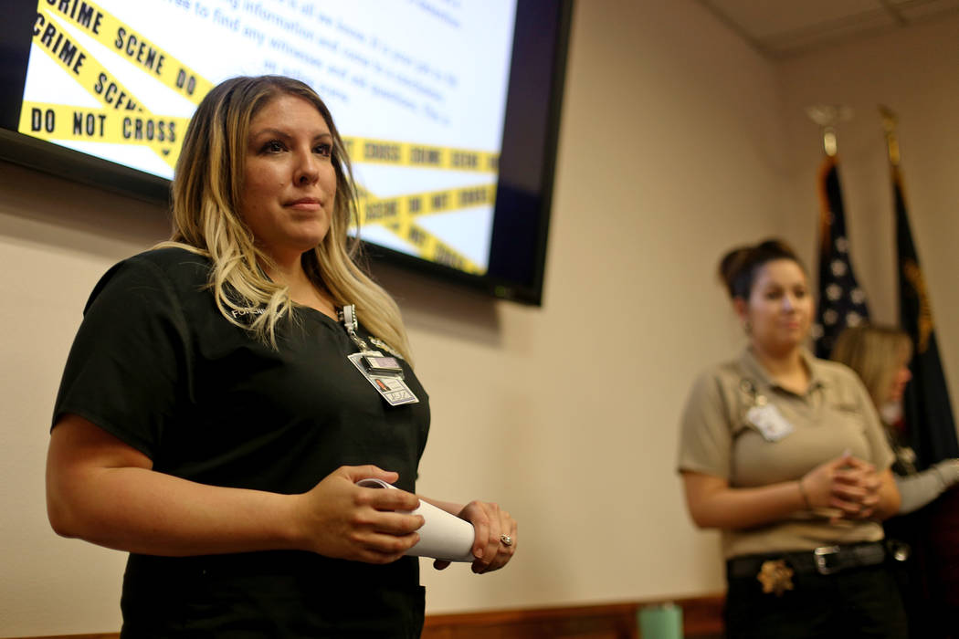 Bri Kinard, from the senior forensic team, talks to kids at the at the coroner office's Take Ou ...