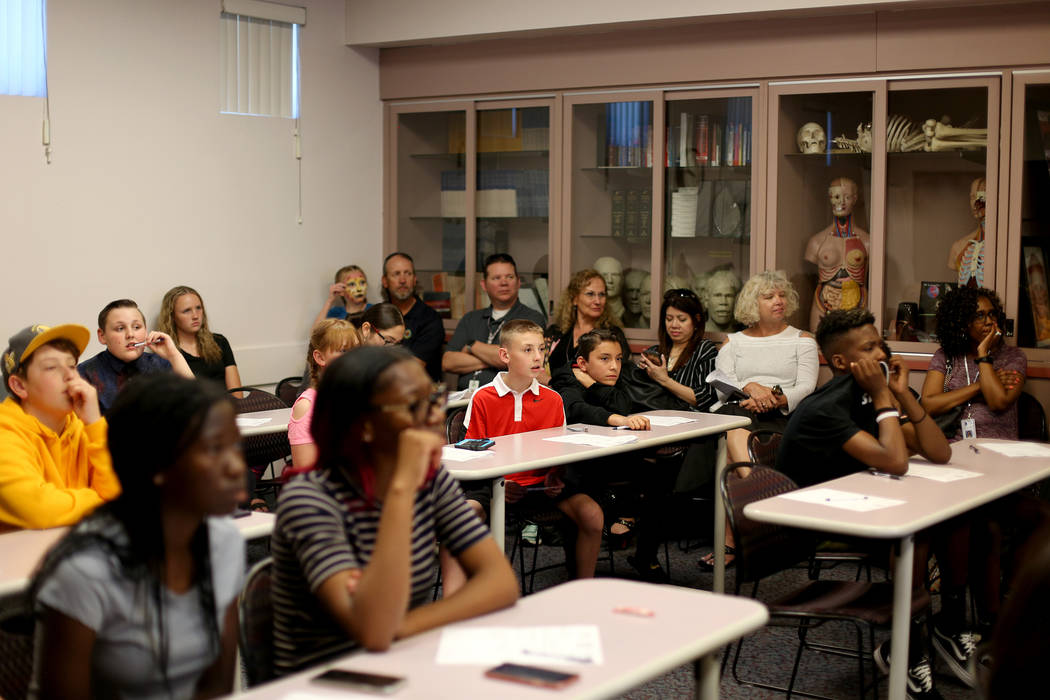 Kids listen to professionals at the at the coroner office's Take Our Daughters and Sons to Work ...