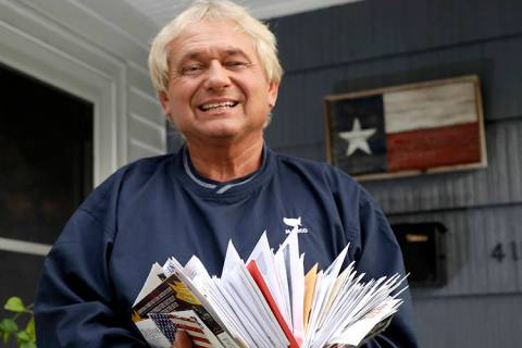 Rex Teter, a member of the Electoral College, holds two days of delivered mail at his home in P ...