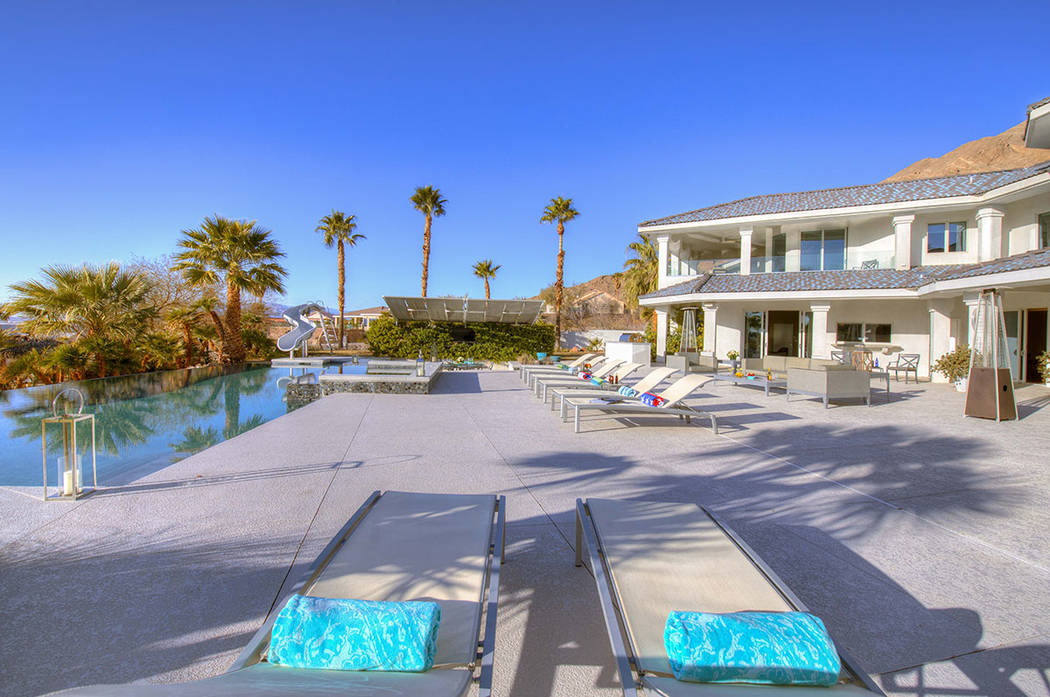 The pool area has a water slide and mature palm trees. (Sotherby's International Realty, Synergy)