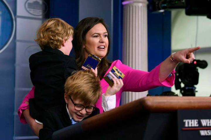 White House press secretary Sarah Sanders, holding her son George and standing next to her son ...