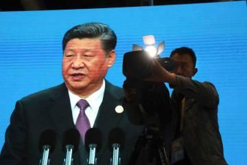 A cameraman films near a screen live broadcasting Chinese President Xi Jinping opening the Seco ...
