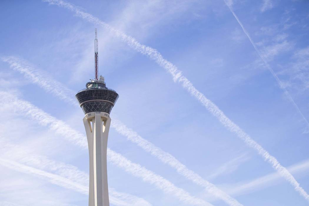 Vapor trails left behind by airplanes are seen above the Stratosphere tower in Las Vegas, Satur ...