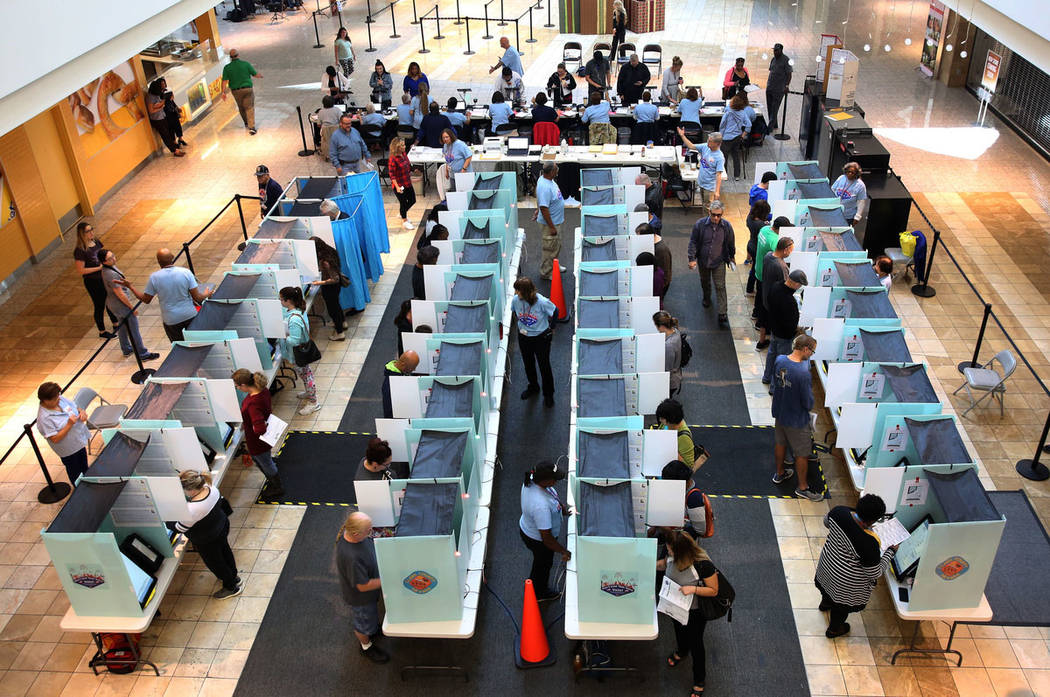 Voters cast their ballots as others sign in at a polling station at Galleria Mall on Tuesday, N ...