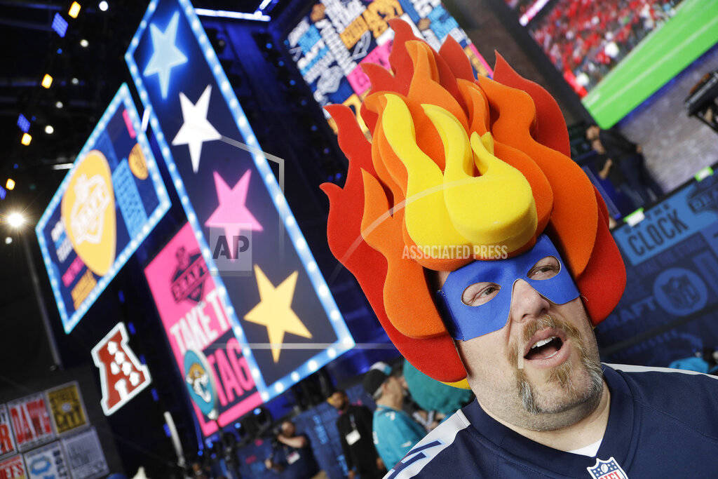 John Davies, of Nashville, Tenn., walks on the main stage before the first round of the NFL foo ...