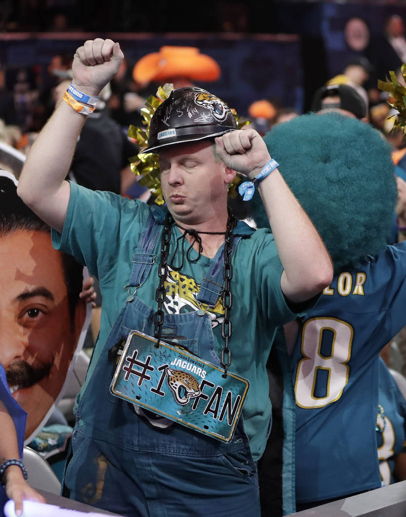 Fans dance near the main stage during the first round at the NFL football draft, Thursday, Apri ...