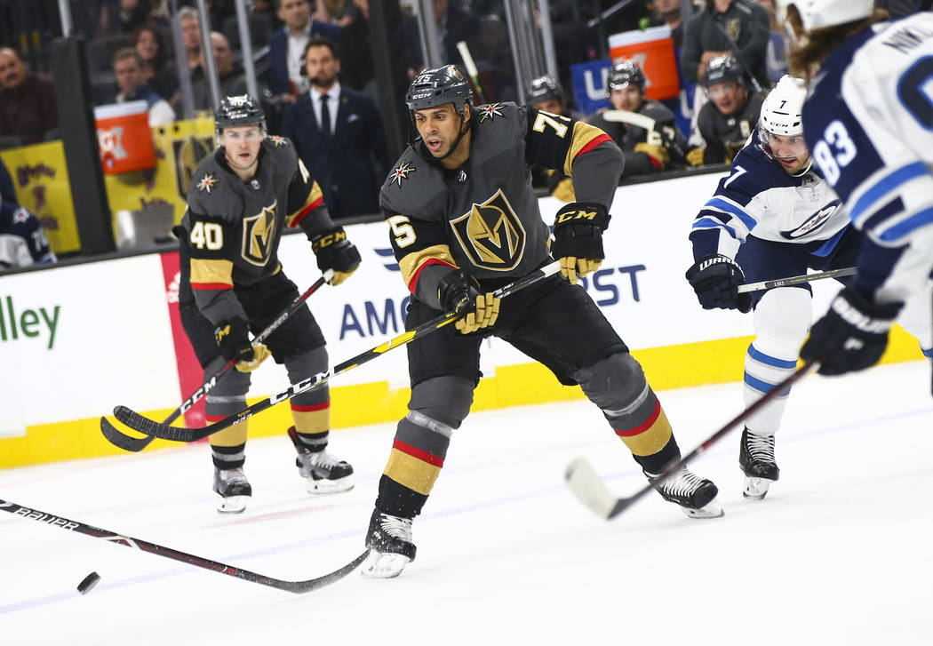 Golden Knights right wing Ryan Reaves (75) passes the puck under pressure from Winnipeg Jets de ...