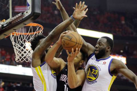 Houston Rockets guard Eric Gordon (10) is stopped by Golden State Warriors defenders Jordan Bel ...