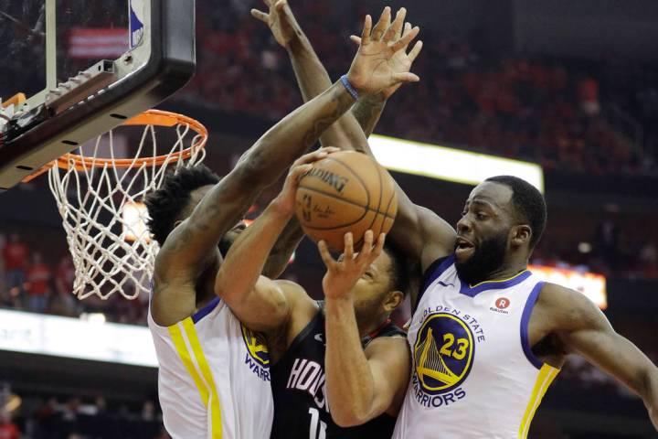 Houston Rockets guard Eric Gordon (10) is stopped by Golden State Warriors defenders Jordan Bel ...