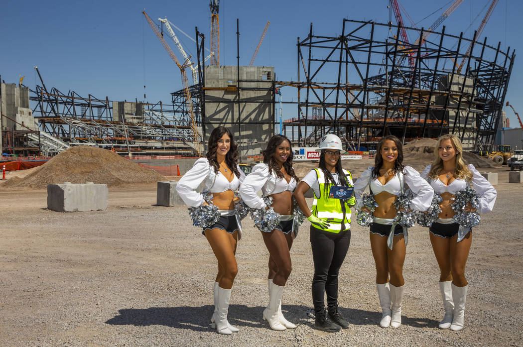 Day laborer Amale Garcia is flanked by the Raiderettes as she helps the Raiders announce their ...