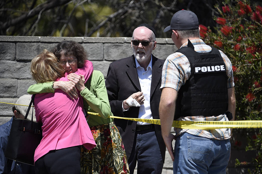 Two people hug as another talks to a San Diego County Sheriff's deputy outside of the Chabad of ...