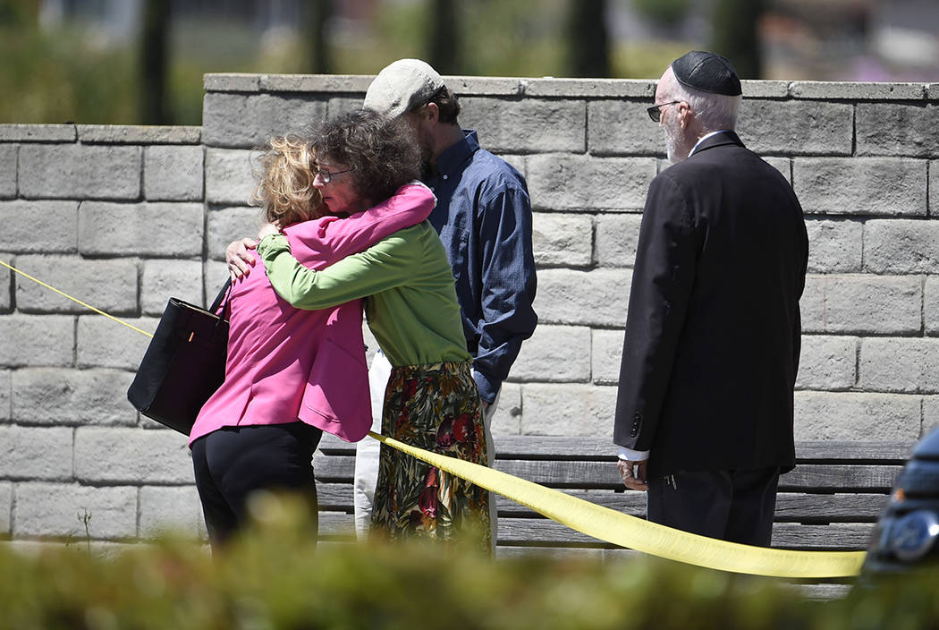Synagogue members console one another outside of the Chabad of Poway Synagogue Saturday, April ...