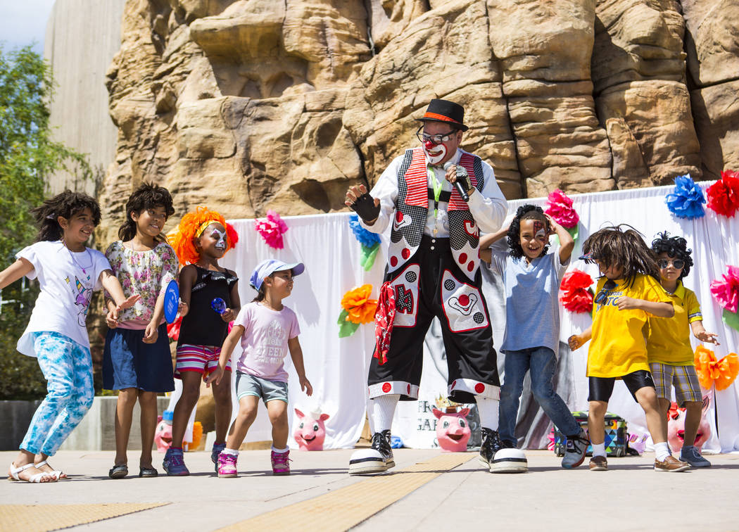 Chirolito the clown leads children in a dance during the 10th annual Dia del Nino event at the ...