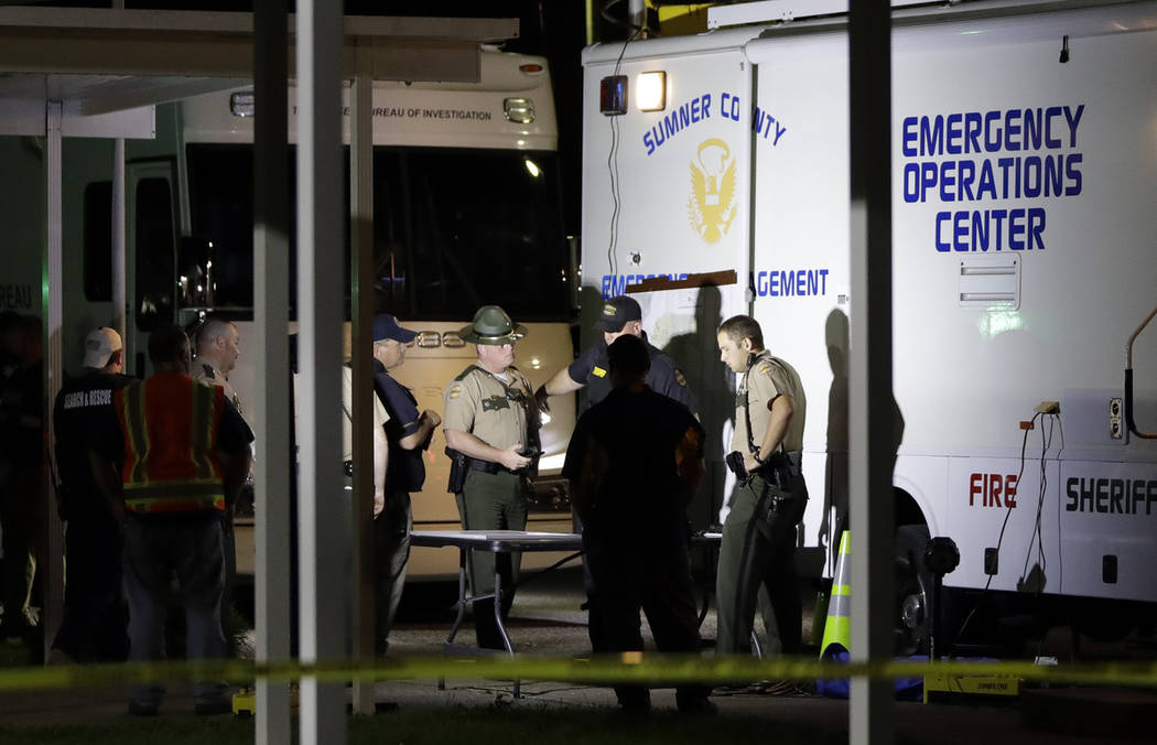 Law enforcement officials work at a command center set up at North Sumner Elementary School Sat ...