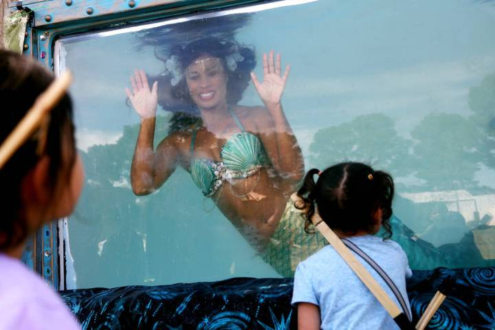 Mermaid Farasha says hi to twins Hanna Sparks, 4, left, and Trinity Sparks, 4, at the Pirate Fe ...