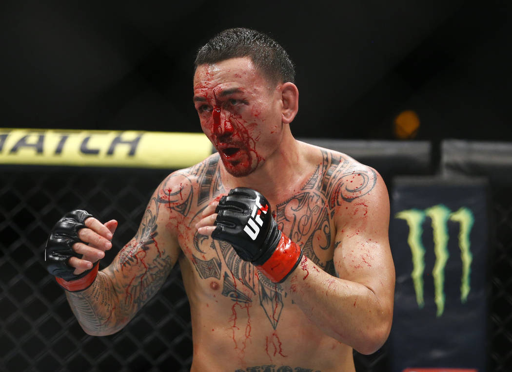 Max Holloway fights Dustin Poirier during an interim lightweight title mixed martial arts bout ...