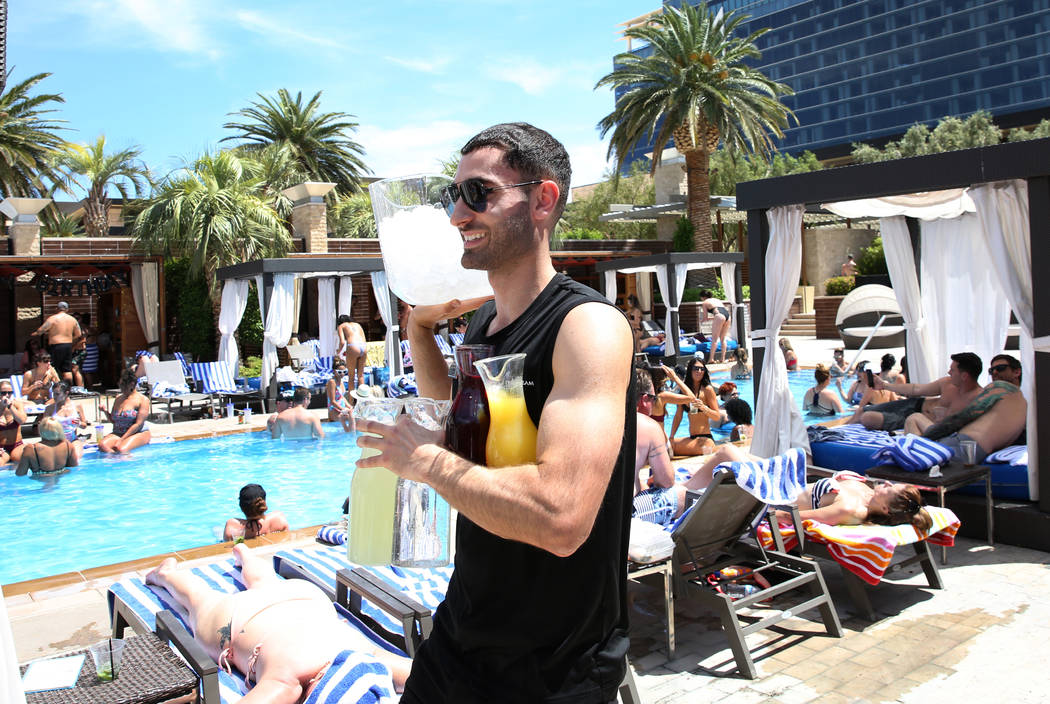Talih Kadi, model cocktail server, carries drinks as he prepares to serve guests at M Resort Sp ...