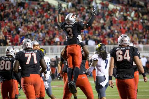 UNLV Rebels running back Lexington Thomas (3) celebrates with teammates after scoring a touchdo ...