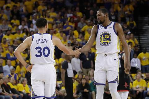 Golden State Warriors guard Stephen Curry (30) reacts with forward Kevin Durant (35) during the ...