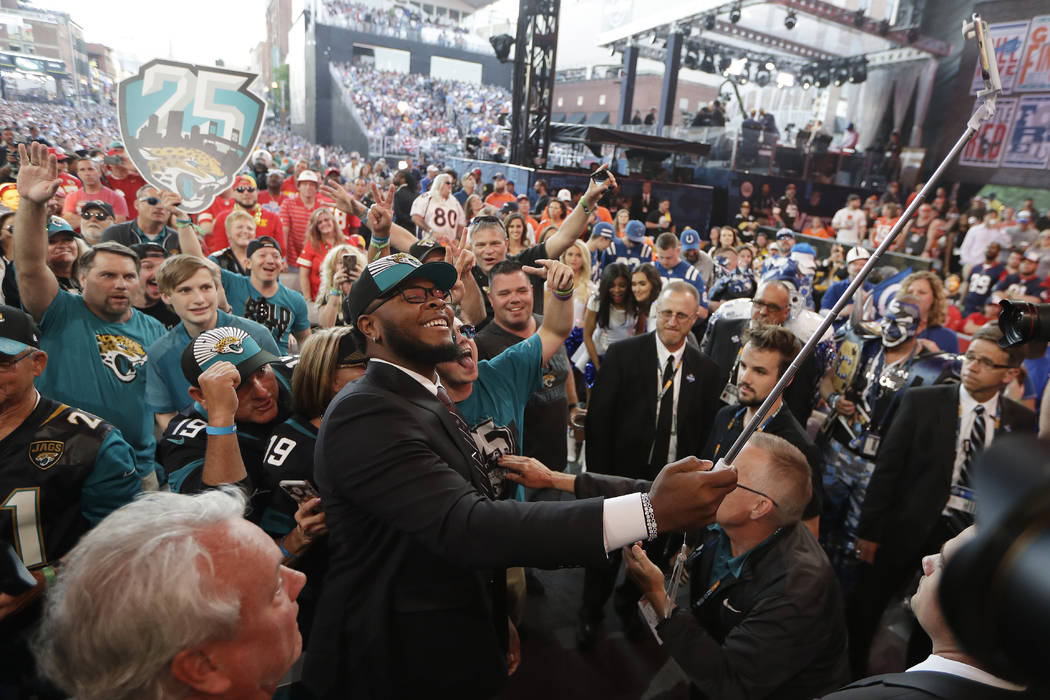 Florida's Jawaan Taylor takes a photo with fans after the Jacksonville Jaguars selected Taylor ...